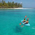Fotografía a un doble kayak sobre aguas cristalinas con una isla tropical al fondo