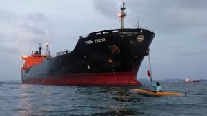 Foto en kayak frente a buque fondeado