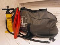 Imagen del kayak en la maleta junto a los remos y el hinchador
